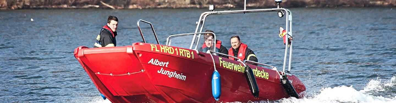 Drei Feuerwehr-Einsatzkräfte fahren in einem Motorboot.