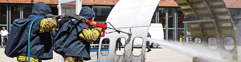 Zwei Feuerwehrleute spritzen ein Flugzeugteil mit Wasser ab.