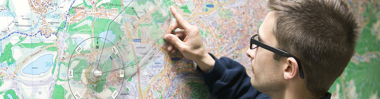 Ein Feuerwehrmann deutet auf einen Punkt auf der Landkarte.