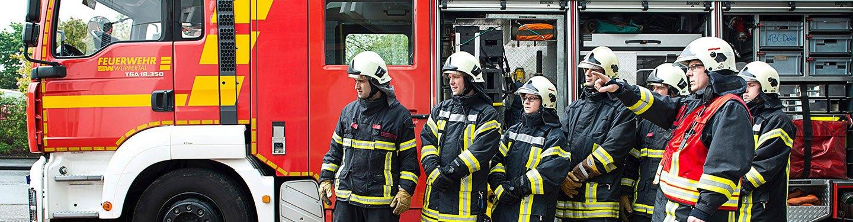 Eine Gruppe von Feuerwehrleuten steht vor einem Löschfahrzeug.