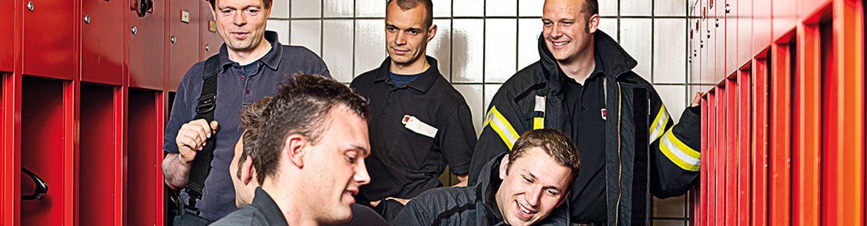 Eine Gruppe von männlichen Feuerwehrleuten unterhält sich in der Umkleidekabine.