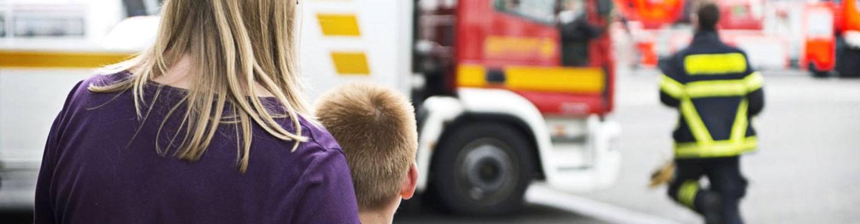 Eine Frau und ihr Sohn sehen einem Feuerwehrmann dabei zu, wie er zum Einsatzfahrzeug sprintet.
