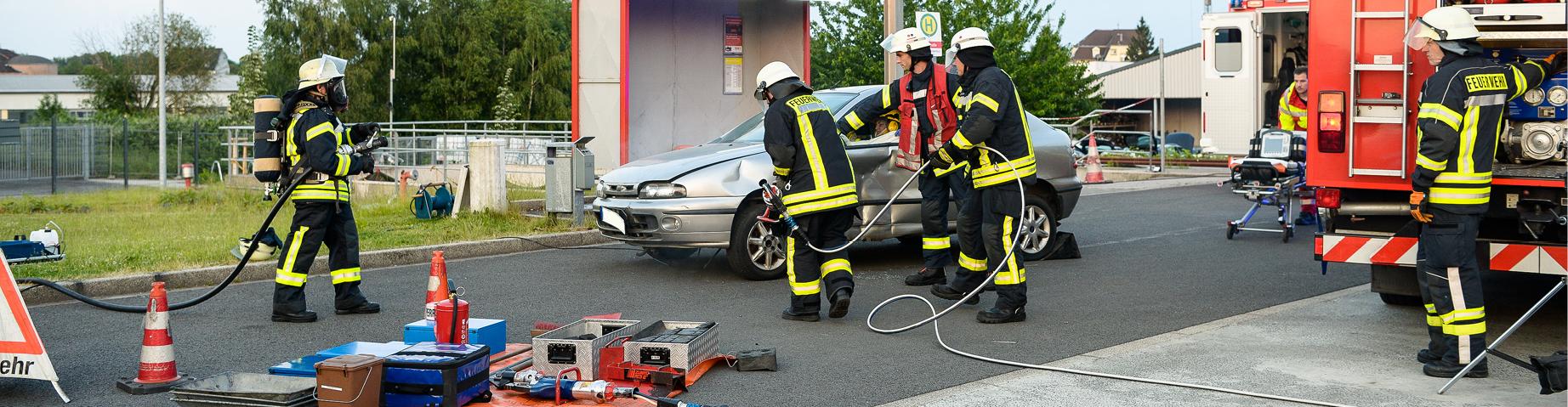 Ein Trupp der Freiwilligen Feuerwehr schneidet ein Auto auf.