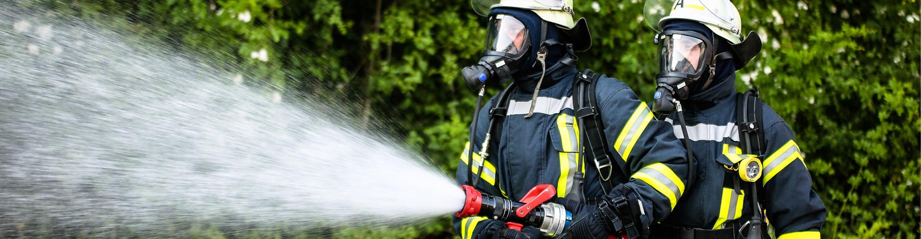 Zwei Feuerwehrmänner beim Löscheinsatz.