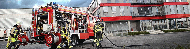 Ein Einsatztrupp der Feuerwehr macht sich vor einem Bürogebäude bereit für Löscharbeiten.